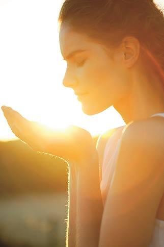 femme qui tient le soleil couchant entre ses mains